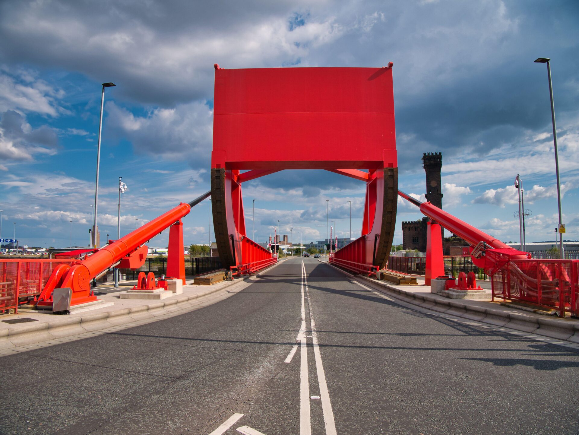 2C762T4 The counterweight and hydraulic rams of a red bascule bridge carrying road and pedestrian traffic across part of the docks complex in Birkenhead, UK.